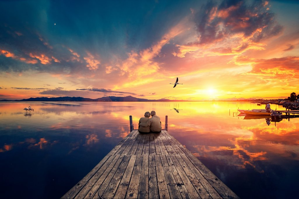 Senior couple sitting on wooden pier looking at colorful sunset near the sea with a flying flamingo reflected on the calm water