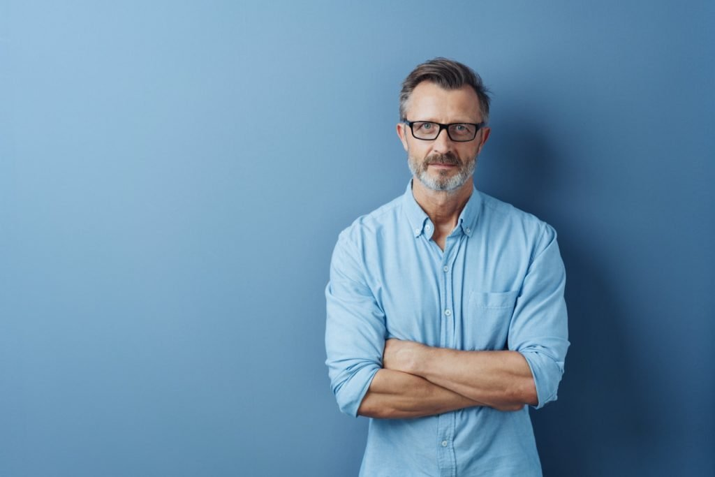 Serious authoritative bearded middle-aged man with folded arms standing looking at the camera against a blue studio background