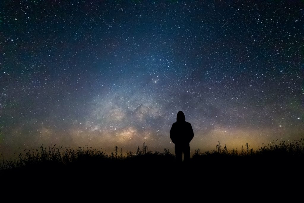 Silhouette of a man watching the milky way stars in summer night sky