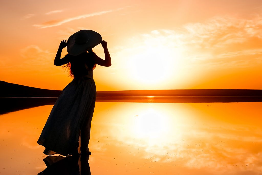 Silhouette of a woman in a dress standing on a lake looking out at the universe during a colorful sunset
