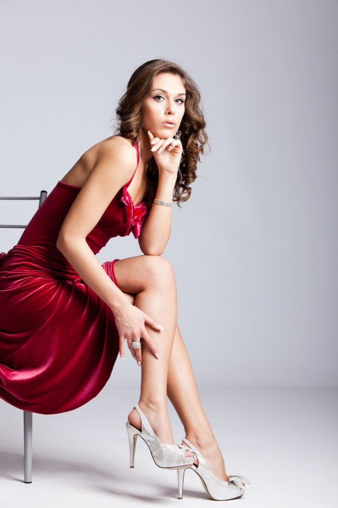 Elegant woman in red dress with silver shoes sitting on chair