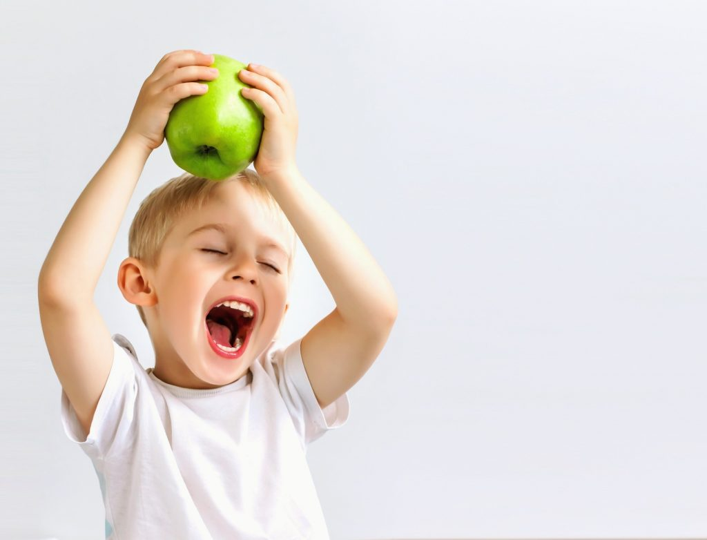 Smiling boy holds a big green apple