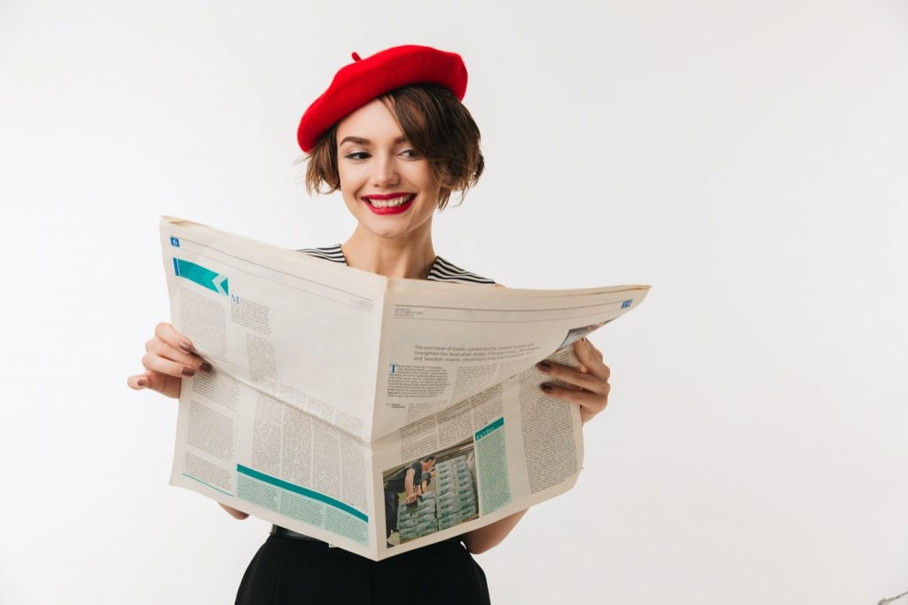 Portrait of a smiling French woman wearing red beret reading newspaper