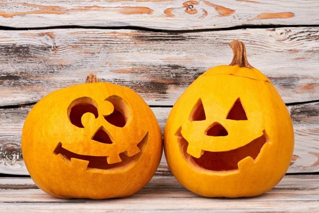 Two Halloween pumpkins on wooden background