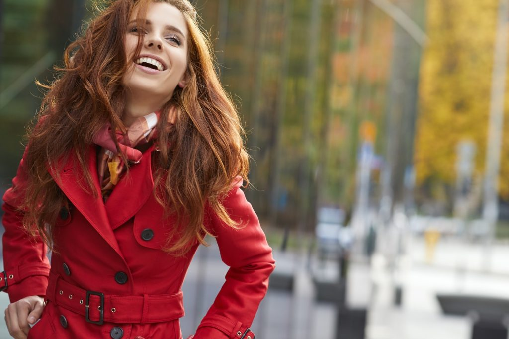 Smiling woman with ginger hair wearing a red coat
