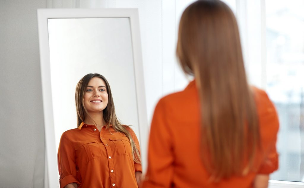 Smiling woman in orange shirt looking at mirror reflection at home or clothing store dressing room