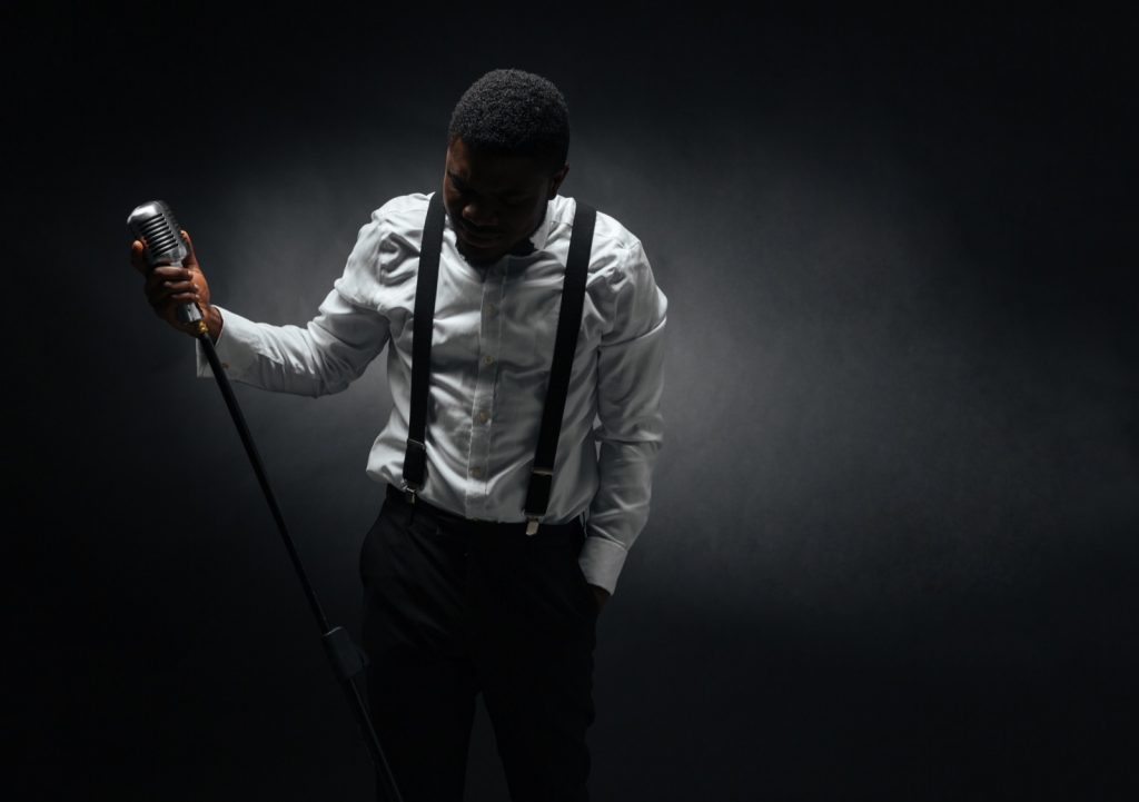 Male singer with microphone posing over black colored background