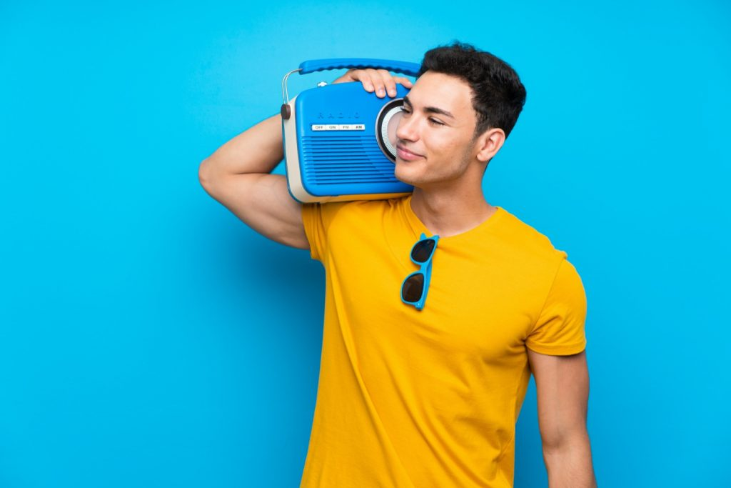 Man on blue background holding a radio on his shoulder