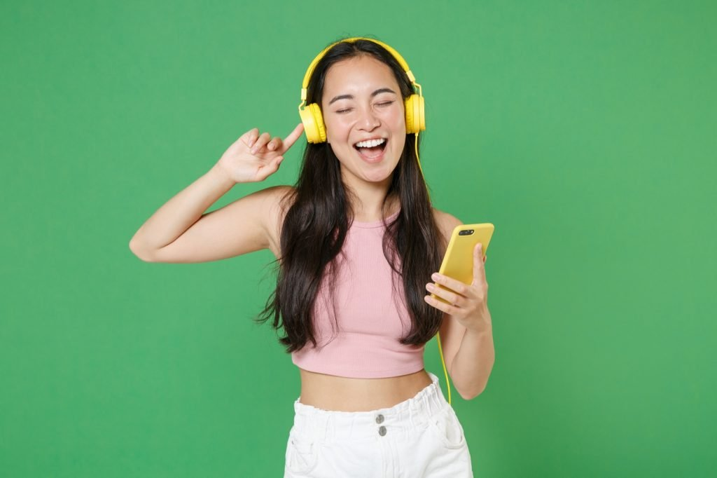Cheerful young woman listening to music with headphones isolated on green background