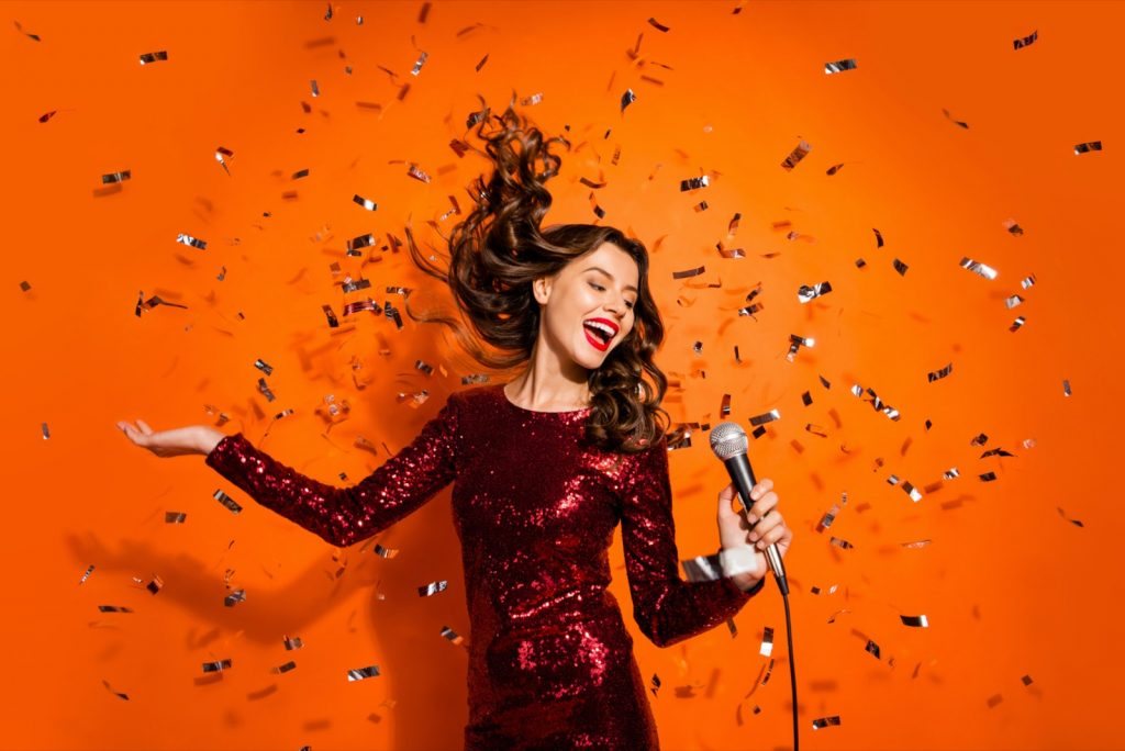 Cheerful girl singing song in a microphone isolated on orange colored background
