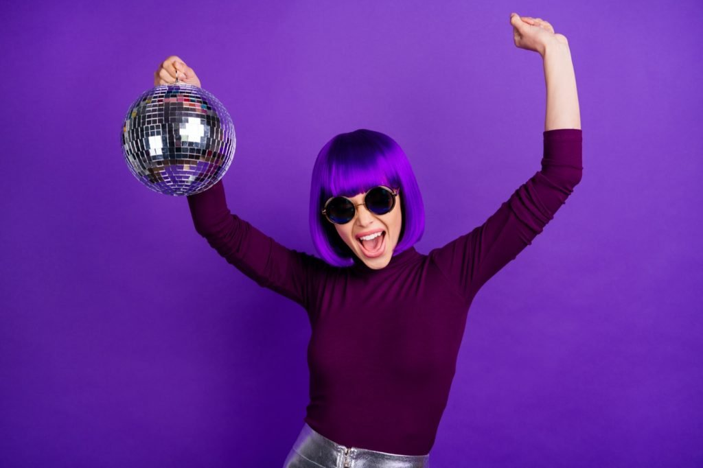 Girl with eyeglasses raising her arms and singing with a disco ball in her hands isolated on purple background
