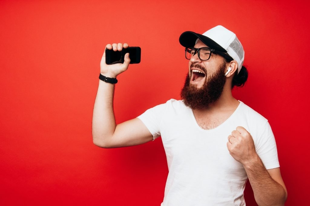 Happy bearded man singing and listening to music with cell phone and wireless earphones isolated on red background