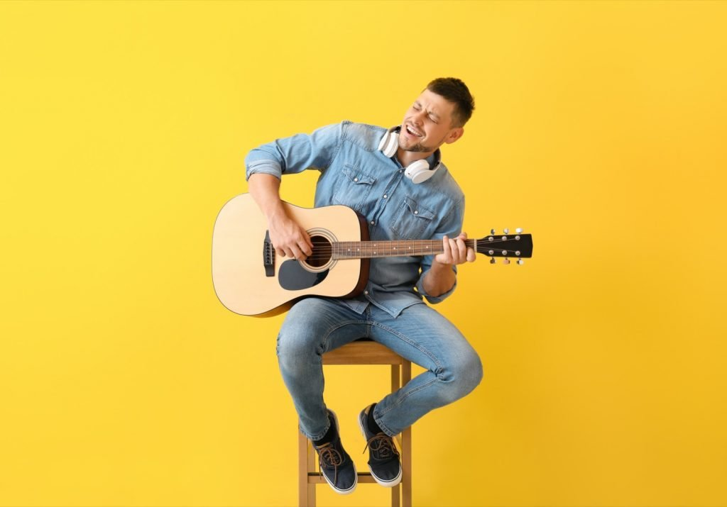 Man playing guitar on yellow colored background