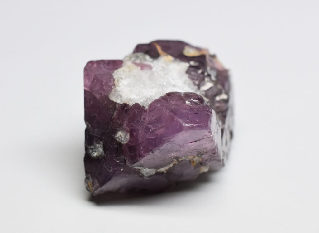 Purple raw spinel stone lies on a grey background