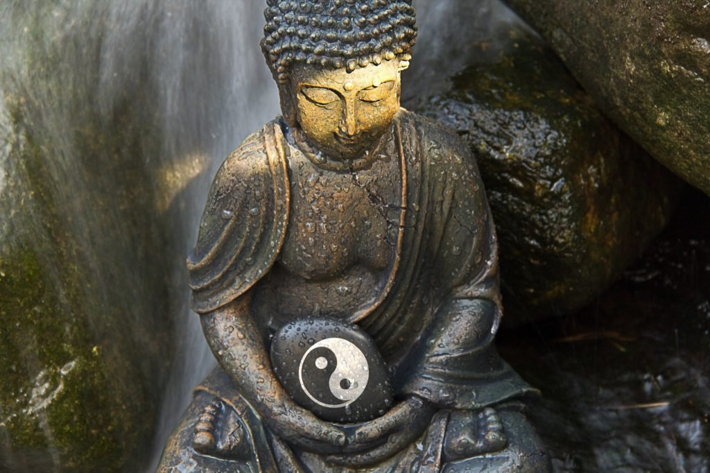 Spiritual Chinese statue holding a Yin Yang symbol in black and white colors