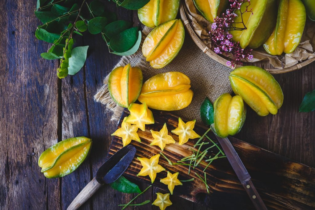 Bunch of starfruits on an old rustic wooden table some are whole and some are cut out into stars