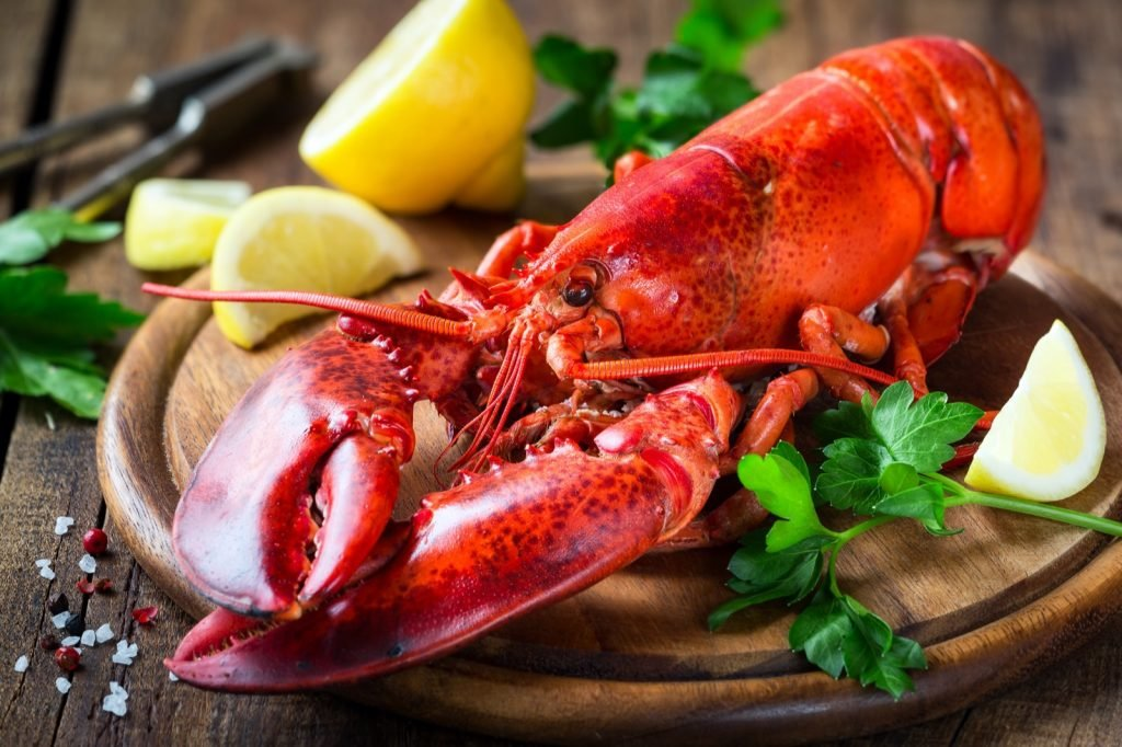 Steamed red lobster on wooden cutting board with parsley and lemon