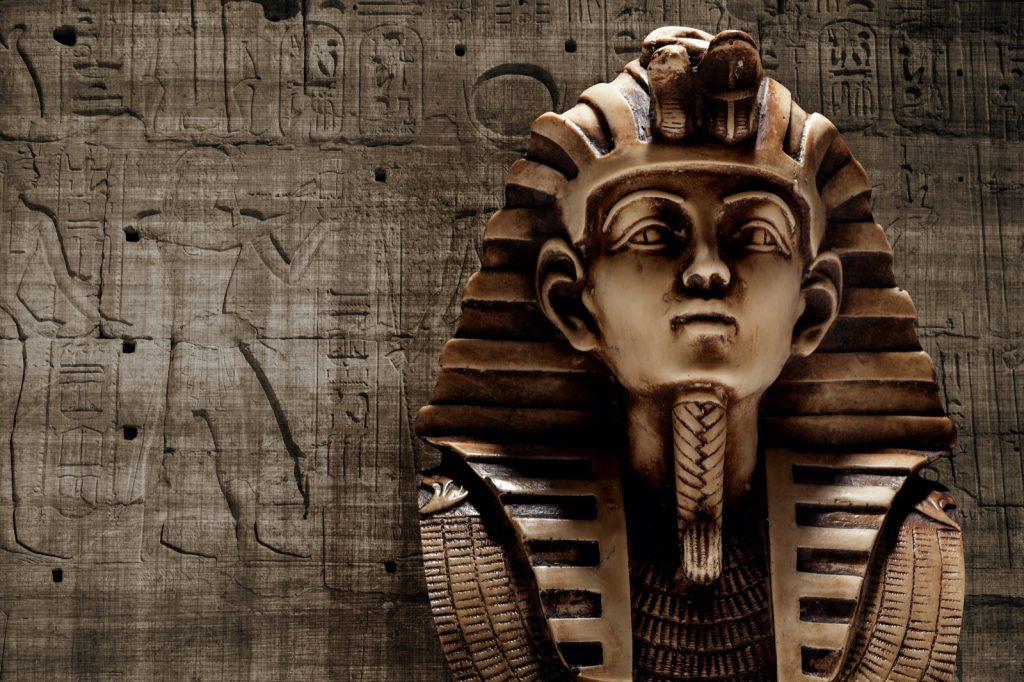 Stone pharaoh Tutankhamun mask on brown colored wall