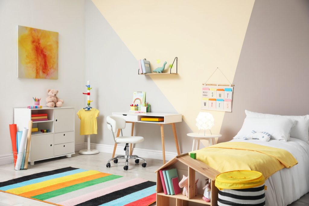 Stylish kids room interior in trendy colors with comfortable bed, desk, and drawer