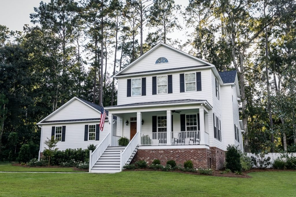 Suburban white colored all American contemporary two story farmhouse with curb appeal