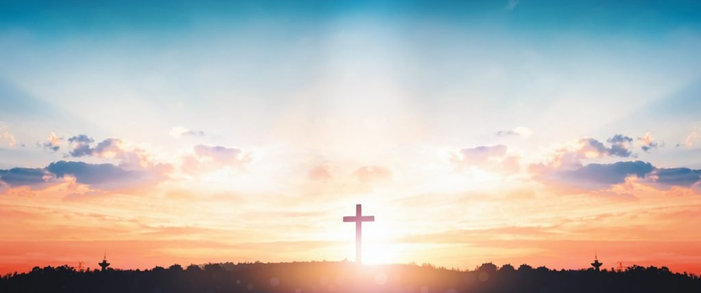 Sunrise with biblical colors and cross symbolizing Jesus Christ