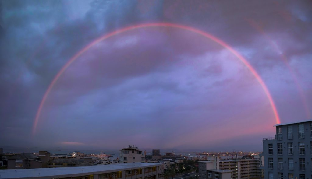 Sunset with red rainbow over cityscape