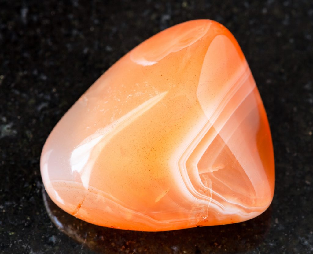 Closeup of a sunstone in different shades of orange, also called carnelian stone