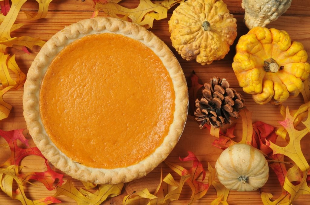 A whole yellow sweet potato pie on an artistic set with autumn leaves, squash and gourds on Thanksgiving
