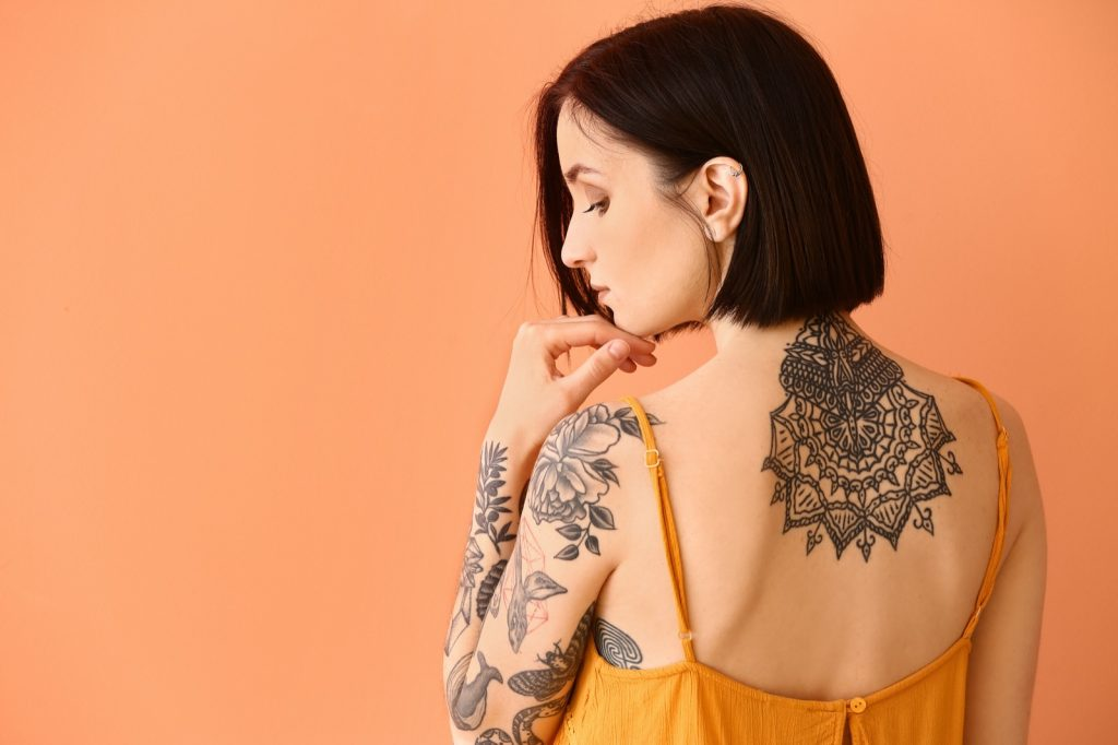 Tattooed woman in orange dress on a peach colored background