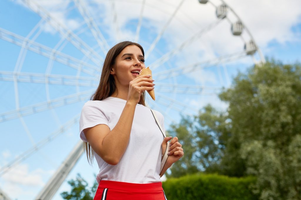 Teen in white shirt cooling down with an ice cream in a theme park