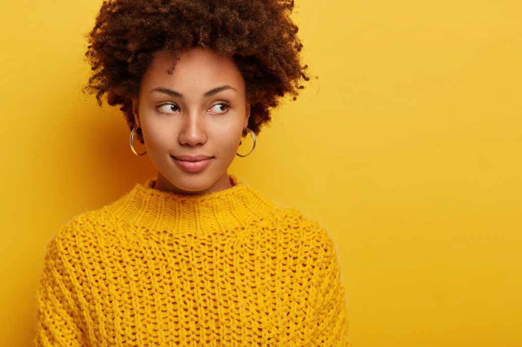 Thoughtful brunette woman in warm sweater on yellow background