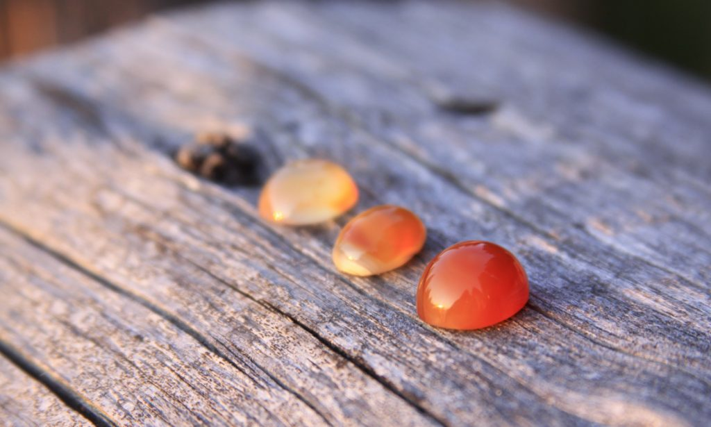 Three orange-red chalcedony agate gemstones on a wooden table