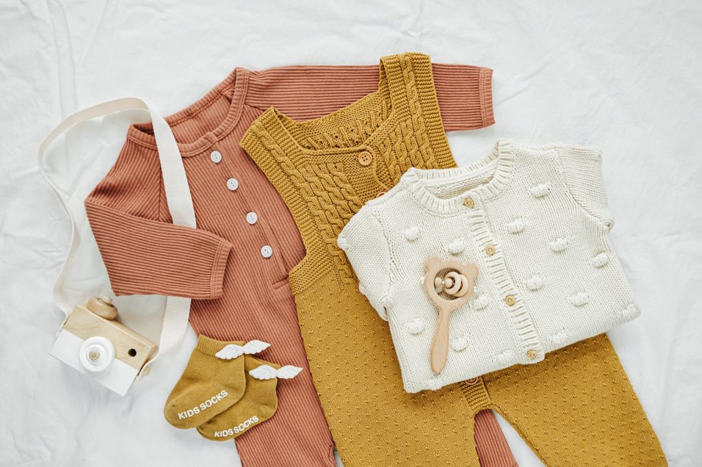 Top view of gender neutral baby clothes in earth tones on white bed