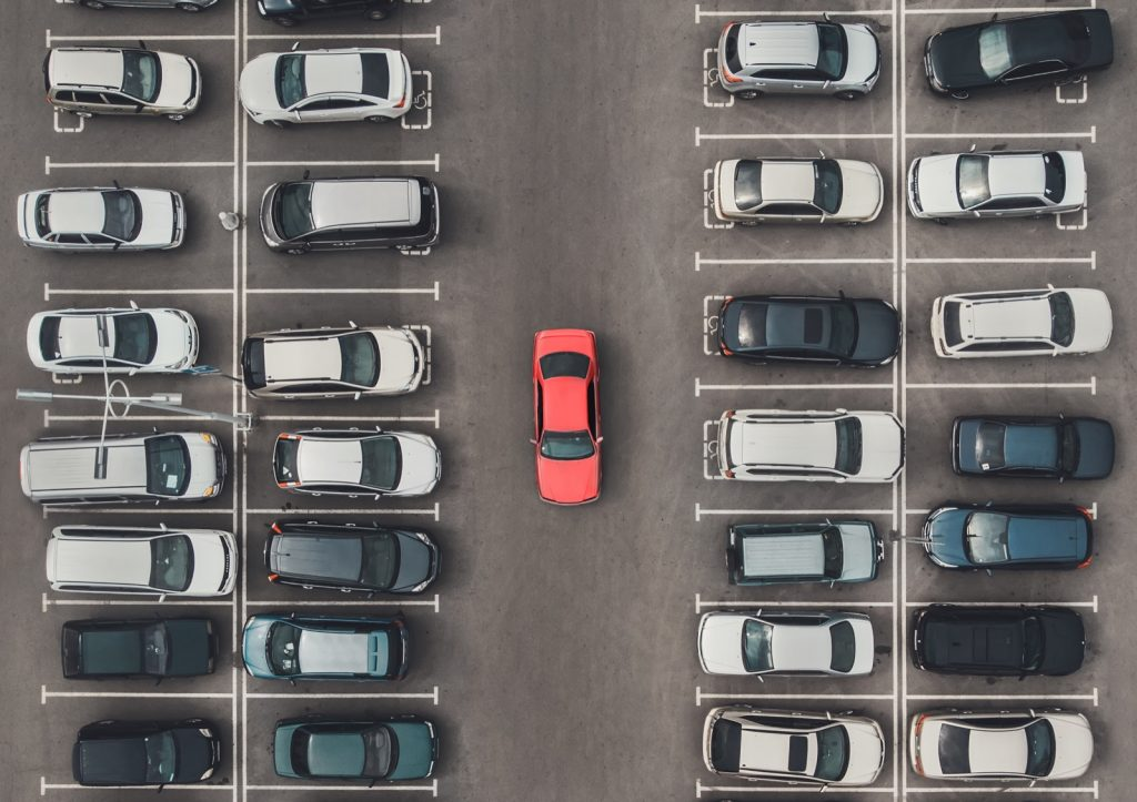 Top view of crowded parking lot with bright red colored car among the grey of mediocre cars