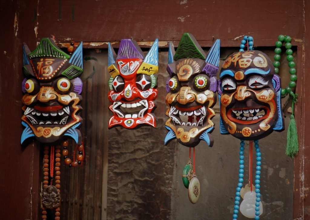 Four traditional wooden Chinese masks hanging next to each other