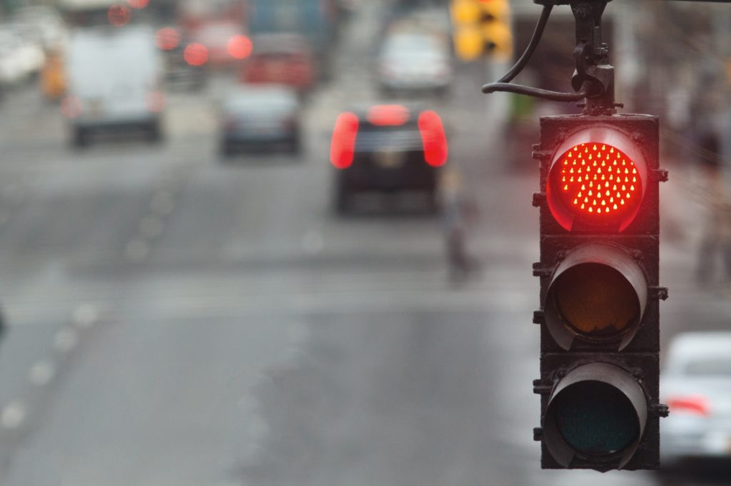 Traffic light on a city road with a red signal