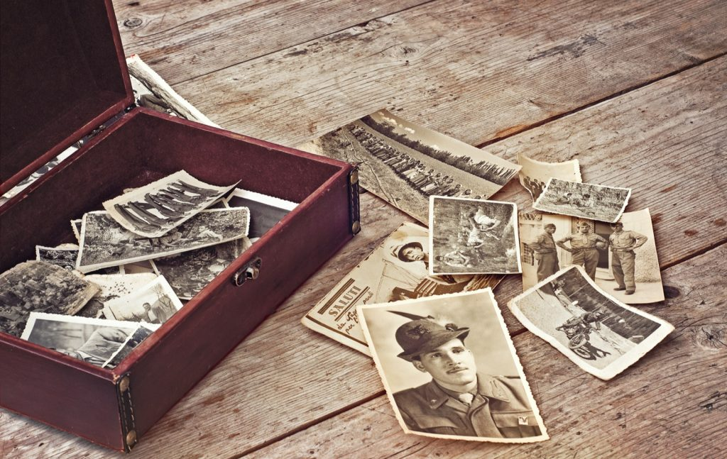 Treasure chest full of memories with old photos on wooden table