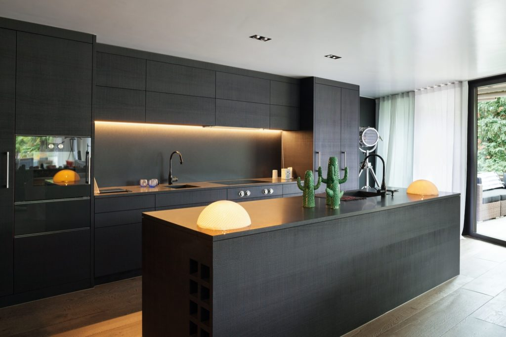 Trendy kitchen with black appliances and wooden floor