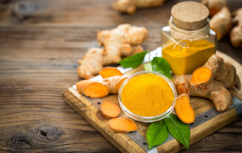Turmeric powder and roots on wooden table