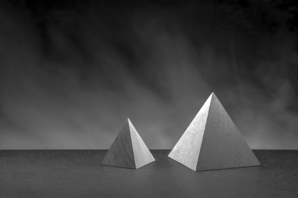 Two gray pyramids as geometric objects on a dark background