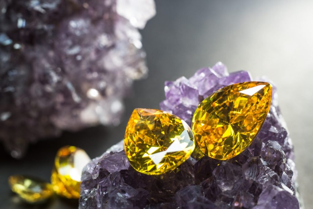 Two teardrop-shaped yellow sapphires resting on top of purple amethyst