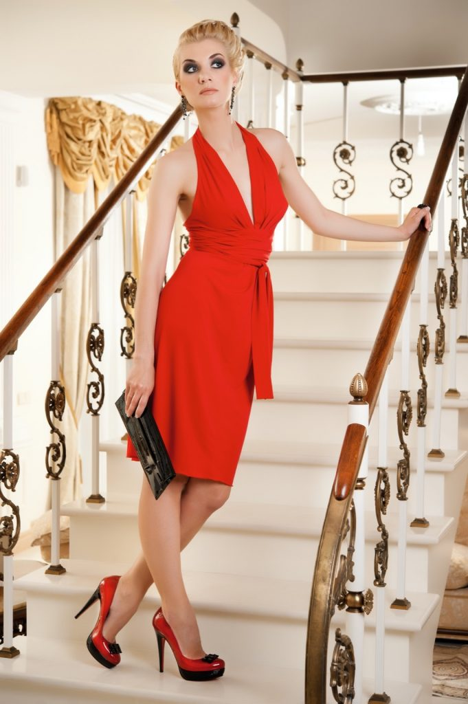 Blond lady standing on a stairs in red dress with black and red two tone shoes