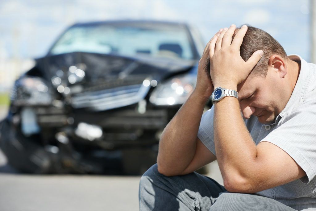 Upset man sitting on the ground holding his head after a car crash