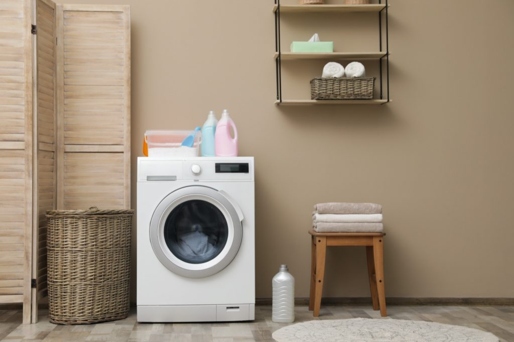 Washing machine near brown colored wall in laundry room