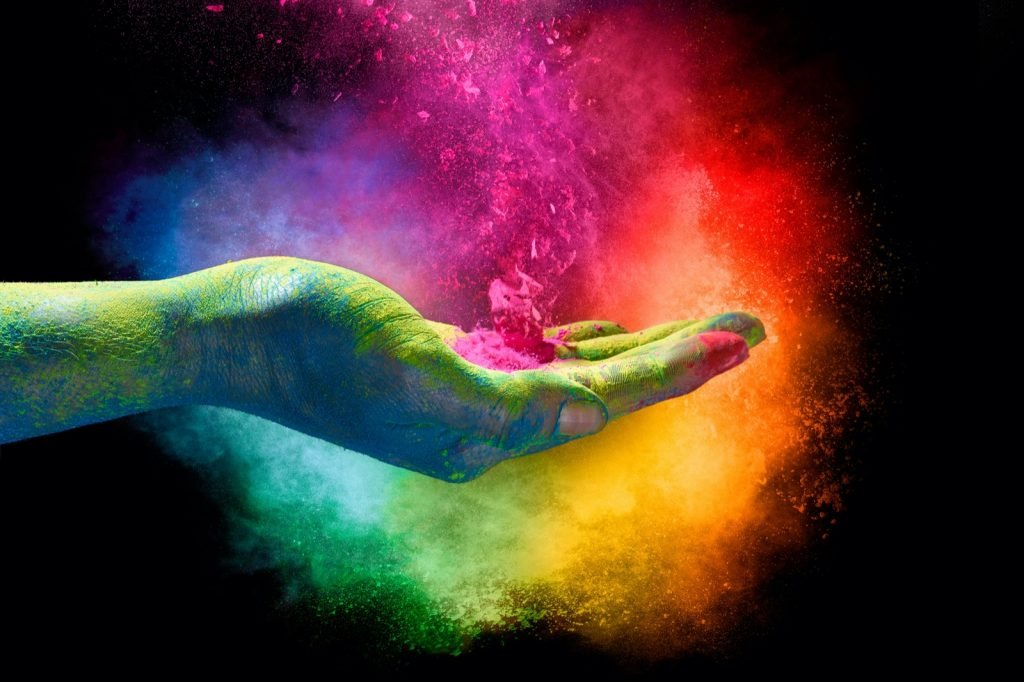 Weird rainbow colored powder exploding from the palm of a hand creating a vibrant cloud of dust in the colors of the spectrum over a black background