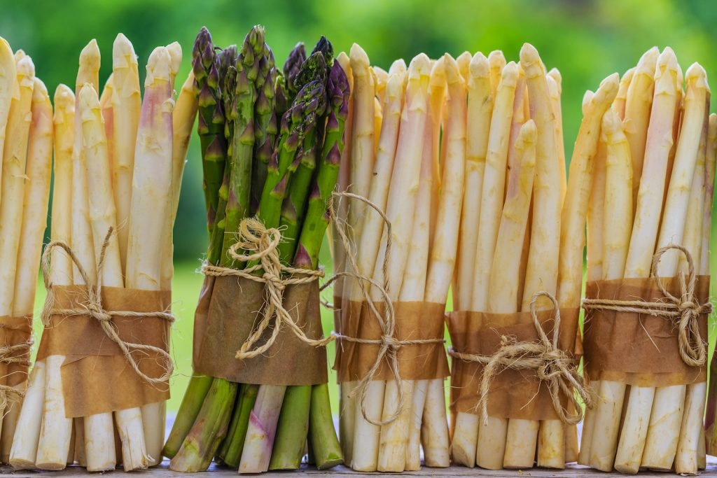 Bunches of white asparagus standing on a table with one green bunch of asparagus among the white