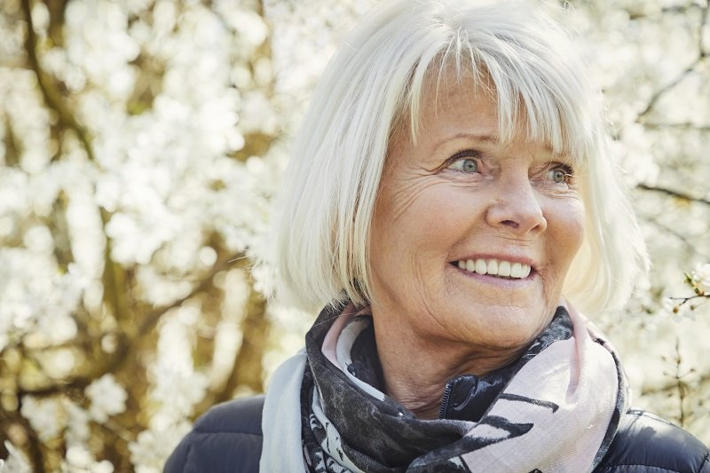 Smiling senior woman in scarf, looking away having white hair