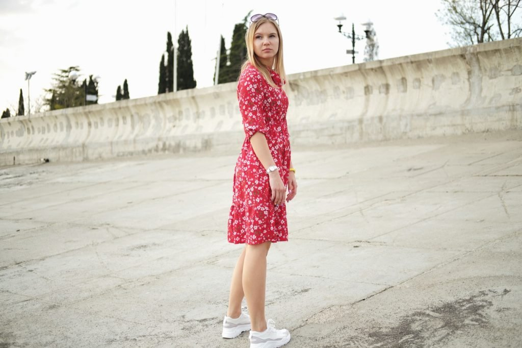 Girl in red dress wearing white sneakers