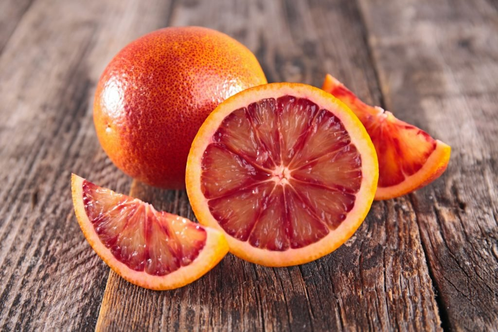 Whole and sliced blood oranges on wooden surface