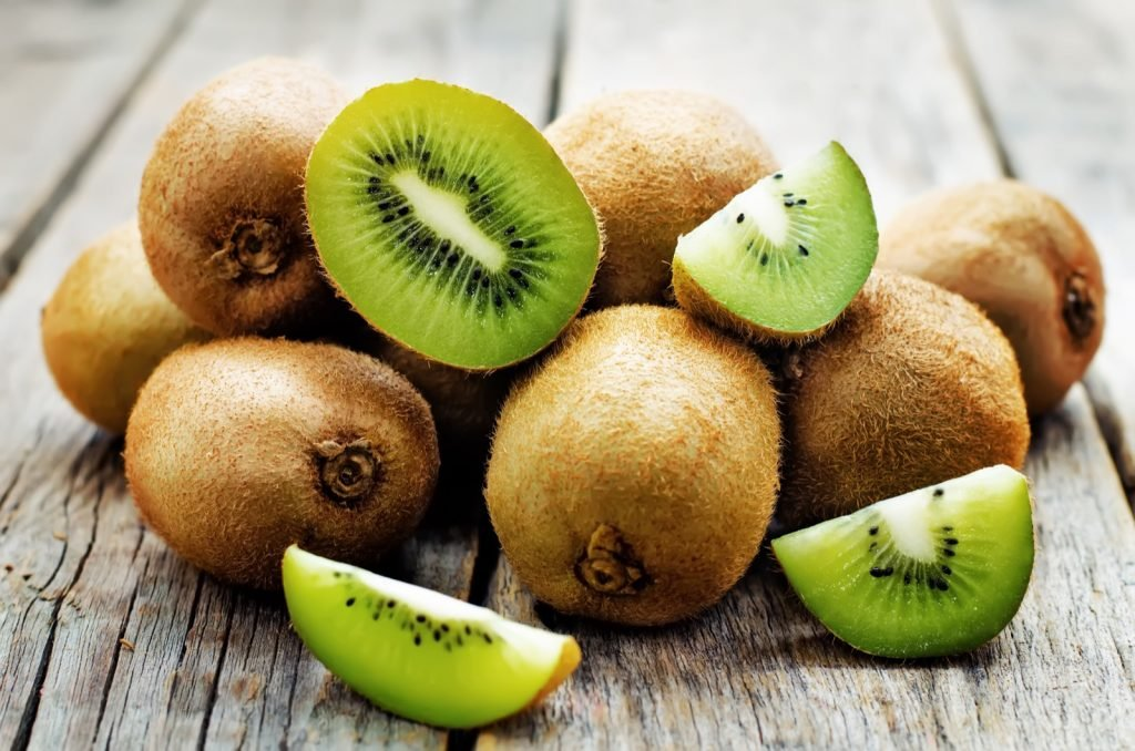 Whole and sliced kiwi fruit on a wooden table